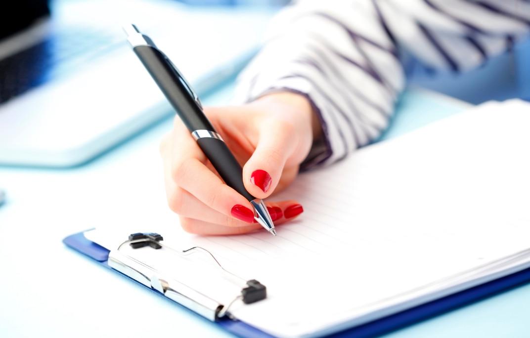 Mão de uma mulher preenchendo formulário em uma prancheta
