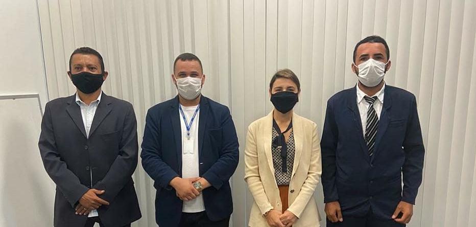Uma mulher e três homens, lado a lado, usando máscaras, em pé, posando para foto