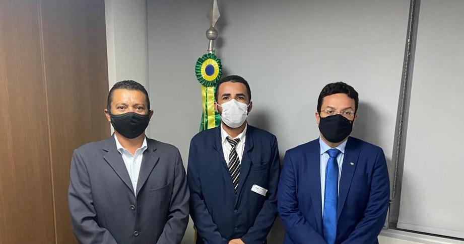 Três homens, lado a lado, trajando terno e usando máscara