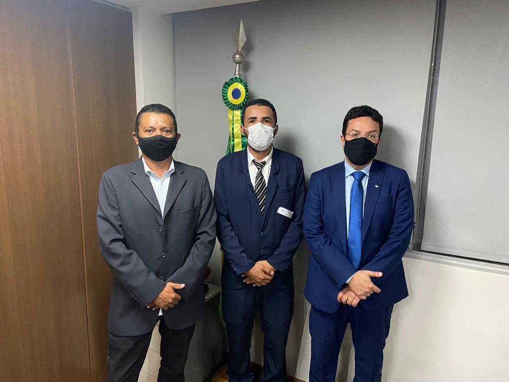 Três homens, trajando ternos e usando máscara, posando para foto